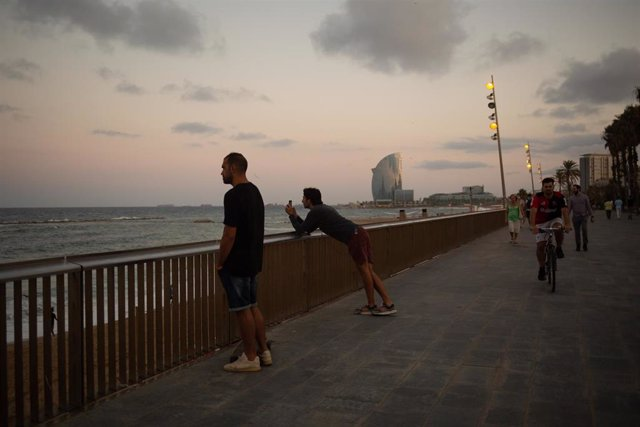 Dos hombres miran el paisaje frente a la playa de la Barceloneta, a 4 de agosto de 2021, en Barcelona, Catalunya (España).