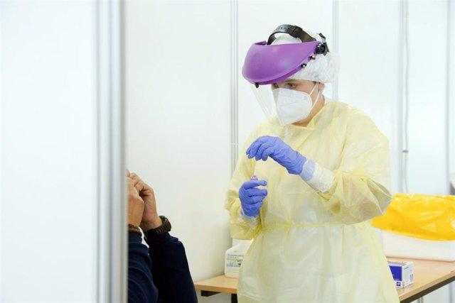 Archivo - Una enfermera realiza una prueba PCR