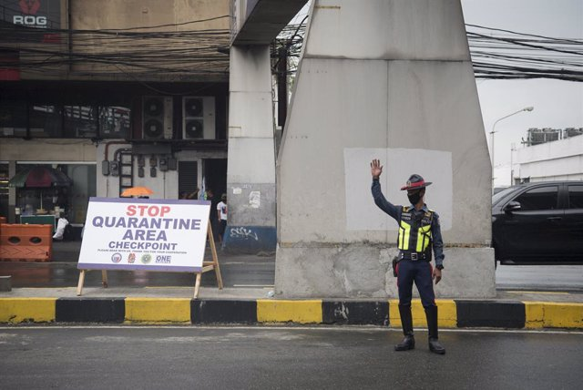 Archivo - 16 March 2020, Philippines, Metro Manila: A police officer wearing a face mask monitors incoming traffic at a checkpoint amid fears pf the spread of Coronavirus (Covid-19). Philippine President Rodrigo Duterte on Monday ordered nearly 60 million
