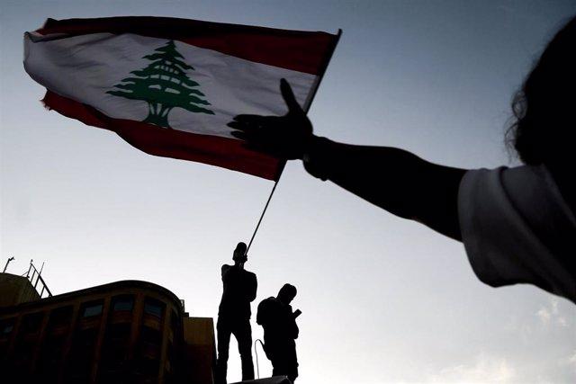 Archivo - Imagen de una bandera siendo ondeada durante una protesta en Líbano