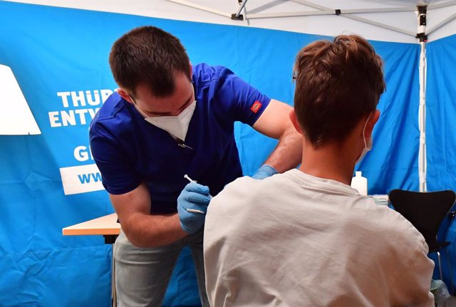 25 August 2021, Thuringen, Erfurt: Johannes Hille (L), medical assistant and paramedic, vaccinates a student with a COVID-19 vaccine d uring a mobile vaccination campaign. Photo: Martin Schutt/dpa-Zentralbild/dpa