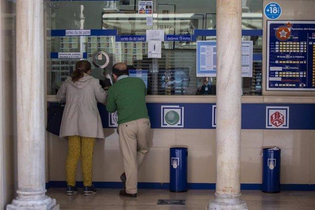 Archivo - Dos personas compran lotería en una Administración.