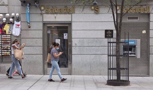 Varias personas pasan por una sucursal de Banco Sabadell, a 2 de septiembre de 2021, en Madrid (España).
