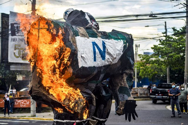 Archivo - 30 July 2021, El Salvador, San Salvador: A paper statue representing militarism is set on fire during a protest against the government of Salvadoran President Nayib Bukele on the 46th anniversary of a government led massacre against peacfully pr