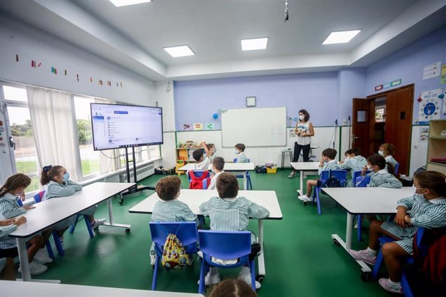 Varios niños escuchan las explicaciones de su profesora en una clase del colegio Virgen de Europa durante el primer día de clase del curso 2021-22, a 6 de septiembre de 2021, en Boadilla del Monte, Madrid (España).