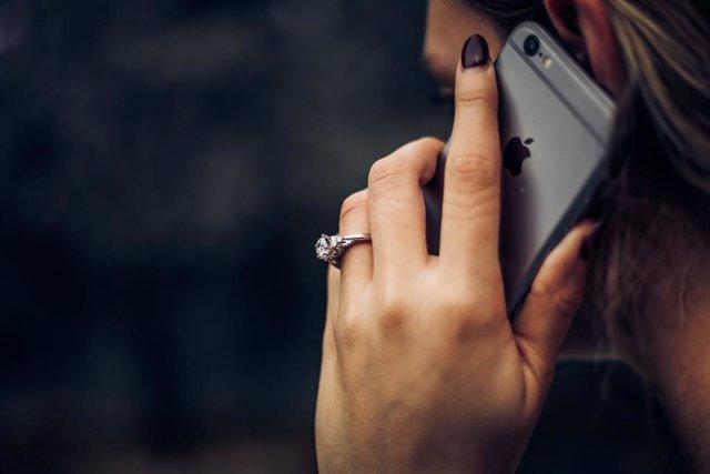 Mujer hablando en un iPhone.