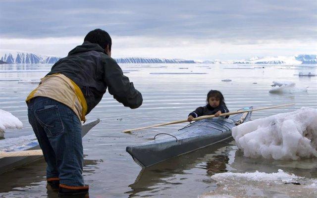 En la foto, un adulto enseña a un niño a remar cerca de Siorapaluk en el noroeste de Groenlandia.