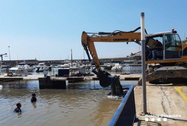 Imatge de la grua que ajuda a restablir la situació al Port d'Alcanar (Tarragona)