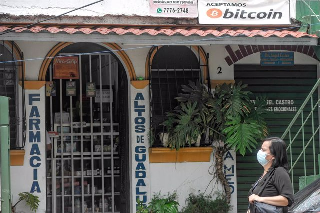 Archivo - 09 June 2021, El Salvador, San Salvador: A woman passes by a local business that accepts bitcoin as a payment method. El Salvador's Congress approved the digital currency Bitcoin as a legal tender, meanwhile, Salvadoran President Nayib Bukele an