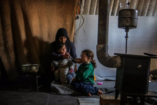 Archivo - 13 March 2021, Lebanon, Aarsal: Haifa, a 23-year-old Syrian refugee woman, feeds her daughter and son inside their tent at the Lebanese town of Aarsal, located north-east of capital Beirut. UNICEF said that after 10 years since the start of the