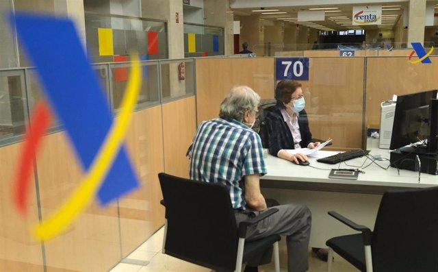 Archivo - Una empleada atiende a una persona de manera presencial desde una oficina de la Agencia Tributaria.