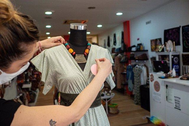 Archivo - Una trabajadora coloca ropa en un maniquí de su establecimiento, foto de recurso