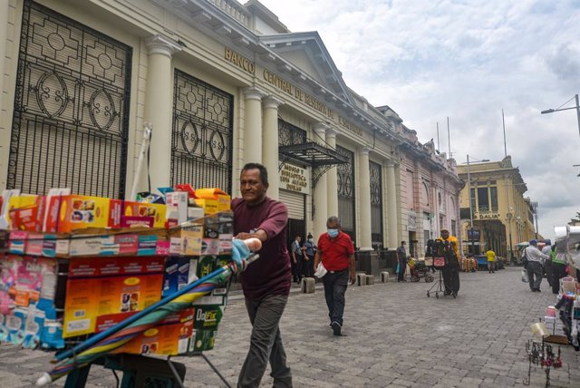 Archivo - 09 June 2021, El Salvador, San Salvador: A man pushes a kart with various items for sale passes by a building of the Central Reserve Bank. El Salvador's Congress approved the digital currency Bitcoin as a legal tender, meanwhile, Salvadoran Pres