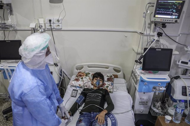 FILED - 25 August 2021, Syria, Salqin: A medic in protective clothing attends to a boy suspected of having contracted coronavirus, inside the intensive care ward of the Syrian American Medical Society (SAMS) Foundation. According to the Early Warning, Ale