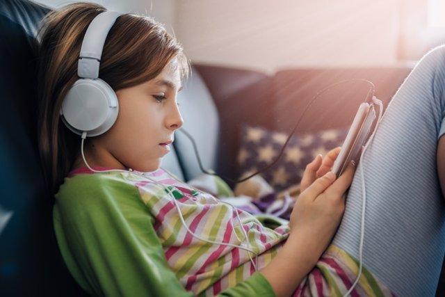 Archivo - Niña adolescente con la tablet y los cascos.