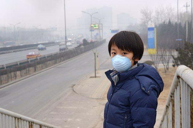 Archivo - Muchacho asiático con máscara bucal contra la contaminación del aire (Beijing)