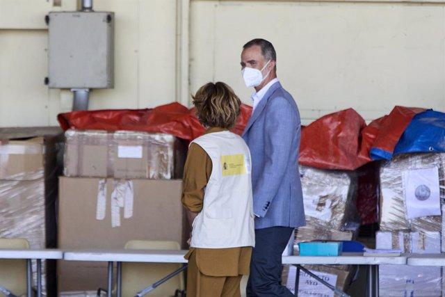El Rey Felipe VI conversa con una cooperante a su llegada al hangar para visitar el dispositivo provisional en Torrejón de Ardoz, a 28 de agosto de 2021, en Torrejón de Ardoz, Madrid, (España). El campamento se ha instalado provisionalmente para recibir a