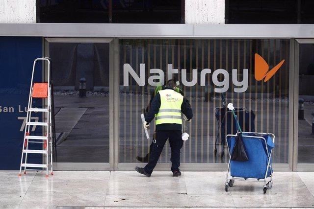 Archivo - Un operario limpia la cristalera de la sede de Naturgy ubicada en la capital, Madrid, (España), a 26 de enero de 2021. IFM Global Infrastructure Fund, asesorado por el gestor de fondos global australiano IFM Investors, ha anunciado este martes u