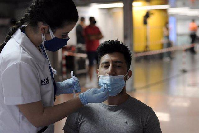 Archivo - Una sanitaria realiza un test de antígenos a un hombre.