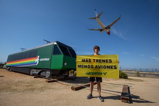 Un activista de Greenpeace subjecta una pancarta en contra de l'ampliació de l'Aeroport de Barcelona - El Prat.