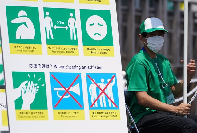 Archivo - 20 July 2021, Japan, Tokyo: A volunteer sits next to a sign warning of COVID-19 countermeasures ahead of the Tokyo 2020 Olympic Games set to place place between 23 July until 08 August 2021. Photo: Mike Egerton/PA Wire/dpa