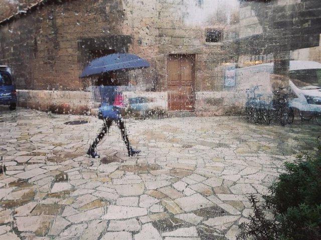 Archivo - Una mujer pasea por el centro de Palma con un paraguas, vista a través de un cristal con gotas de lluvia.