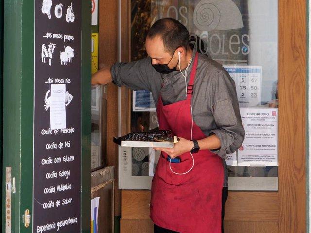 Un camarero junto a varias indicaciones de obligatoriedad de presentar certificados antes de acceder al interior, en una marisquería de la Rua da Raiña, el día en que el TSXG declara nula la petición de certificado Covid para entrar en hostelería, a 12 de