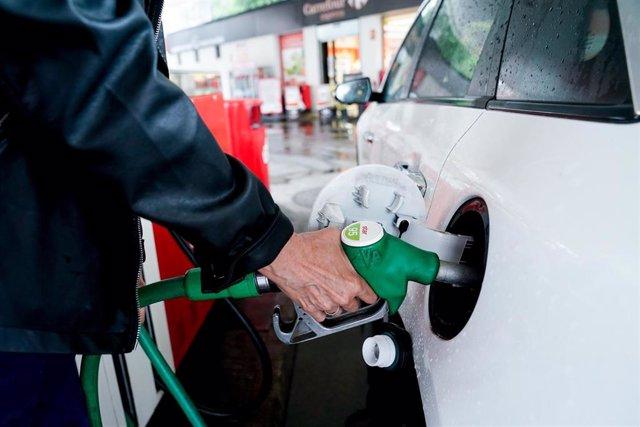 Archivo - Una mujer pone gasolina a su vehículo en una gasolinera