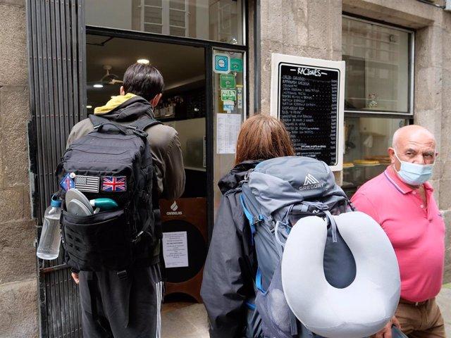 Archivo - Dos peregrinos frente a un local de hostelería, a 31 de julio de 2021, en Santiago de Compostela
