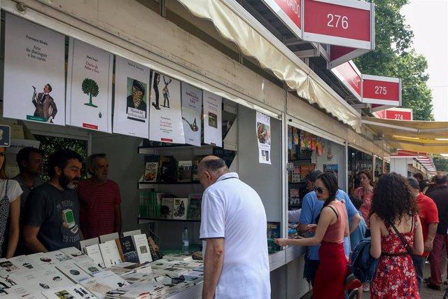 Archivo - Visitantes se acercan a las casetas de la Feria del Libro de Madrid.