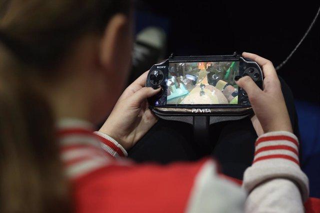 Archivo - Niña juega con dispositivo móvil, videojuego