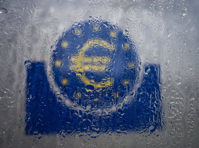 Archivo - FILED - 19 March 2020, Hessen, Frankfurt_Main: Water droplets slide down the glass covering the euro symbol at the south entrance to the headquarters of the European Central Bank (ECB). The global economy will contract 3 per cent this year due t