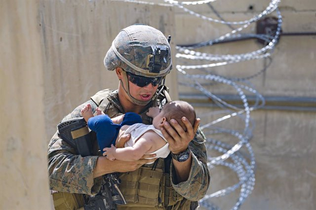 HANDOUT - 21 August 2021, Afghanistan, Kabul: A US marine soldier carries a young boy at the Hamid Karzai International Airport during the evacuation of civilians following the Taliban takeover. Photo: Lcpl. Nicholas Guevara/U.S. Mari/Planet Pix via ZUMA