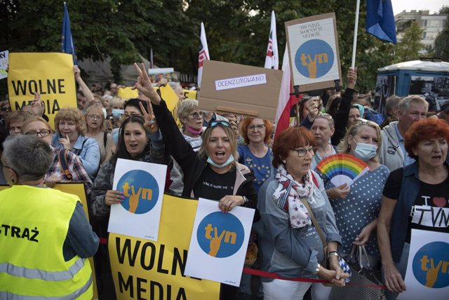 10 August 2021, Poland, Warsaw: People shout slogans and hold placards with the independent broadcaster TVN logo during a protest in front of the Polish Parliament (Sejm) as part of a nationwide protest against a proposed bill by the lawmakers of the ruli