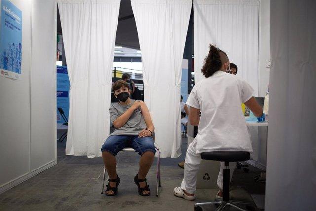 Archivo - Un adolescente recibe la vacuna contra el Covid-19 en el recinto de Montjuïc de Fira de Barcelona, a 4 de agosto de 2021, en Barcelona, Catalunya, (España).