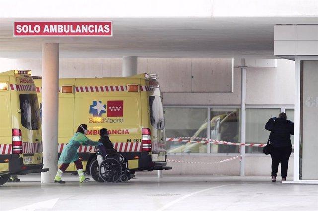 Archivo - Una sanitaria protegida con guantes y mascarilla empuja una silla de ruedas con un paciente en la entrada de Urgencias del Hospital de Fuenlabrada, junto al que se está montando un Hospital de campaña que contará con 750 metros cuadrados y 50 ca