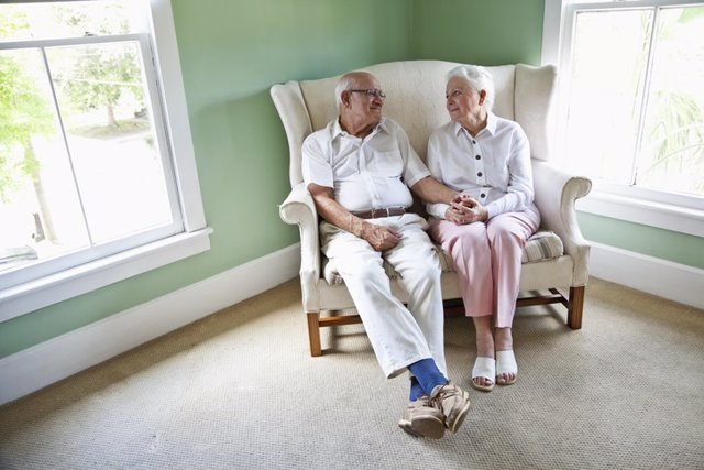 Archivo - Elderly couple sitting together on love seat