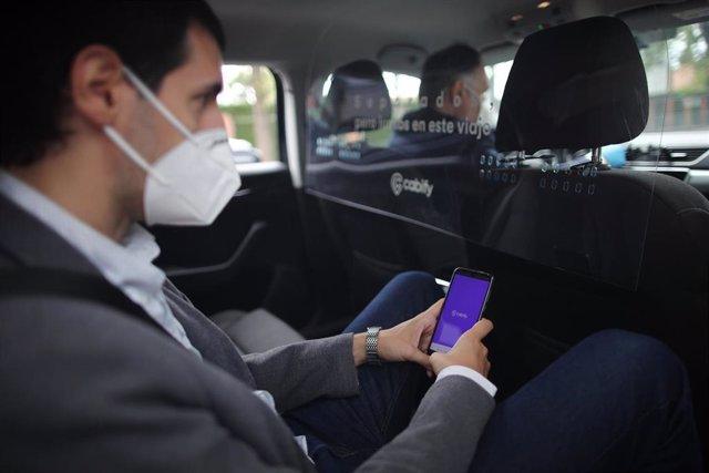 Archivo - Un cliente protegido con mascarilla viaja en un coche conducido por un trabajador protegido con mascarilla .