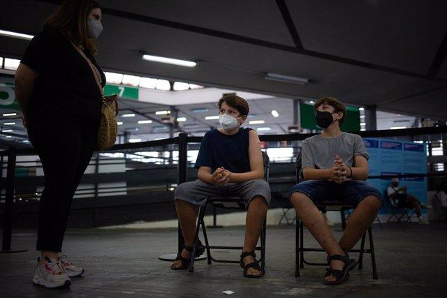 Archivo - Arxiu - Dos adolescents esperen per rebre la vacuna contra la covid-19 al recinte de Montjuïc de Fira de Barcelona