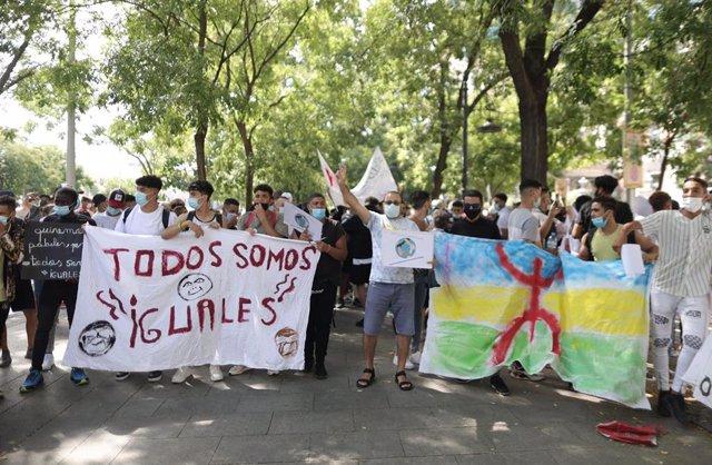 Varias personas con una pancarta en la que se lee: `Todos somos iguales, en una concentración frente al Ministerio del Interior para exigir la reforma del Reglamento de Extranjería.