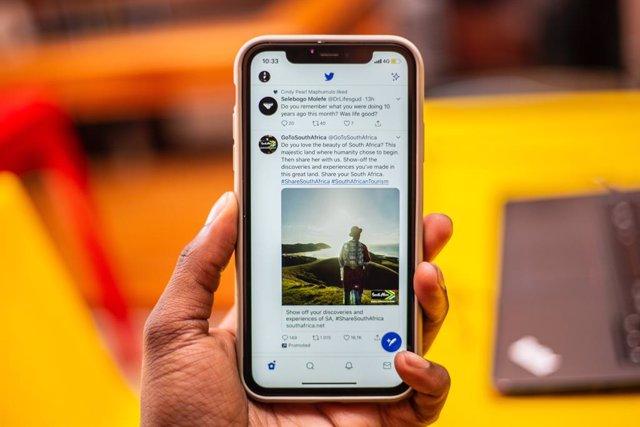 Archivo - Hombre sujetando un iPhone con la interfaz de Twitter