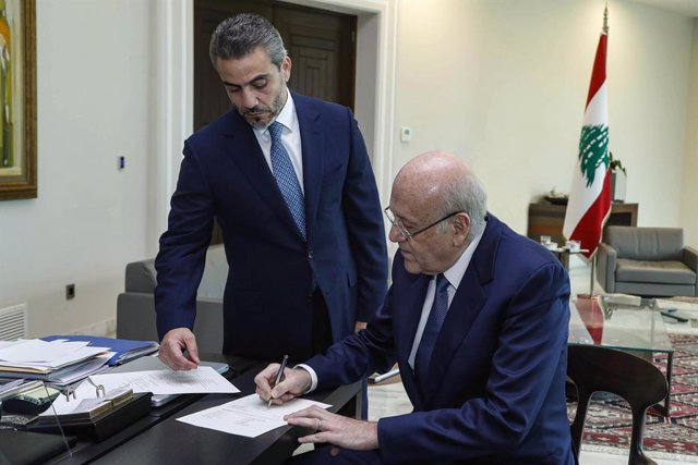 HANDOUT - 10 September 2021, Lebanon, Baabda: Lebanese Prime Minister Najib Mikati (R) signs a decree to form a long-awaited government comprising 24 ministers in an effort to tackle the country's worst economic crisis since the 1975-1990 civil war ended.
