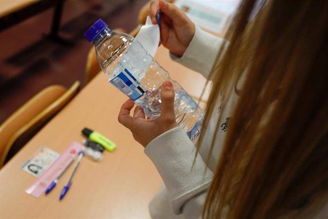 Archivo - Una joven despega el papel de la botella cumpliendo las normas a seguir para la convocatoria extraordinaria de la Evaluación del Bachillerato para el Acceso a la Universidad (EBAU), a 6 de julio de 2021, en Madrid, (España). Un total de 6.213 al