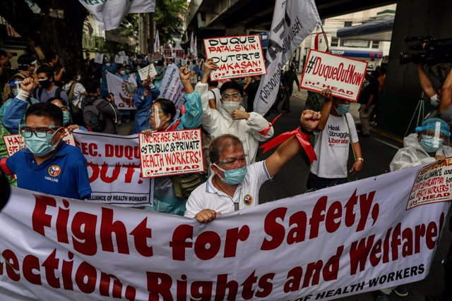 01 September 2021, Philippines, Manila: Hospital workers and health activists hold signs during a protest in front of the Department of Health headquarters in Manila demanding for the immediate release of COVID-19 funds allocated for support to healthcare