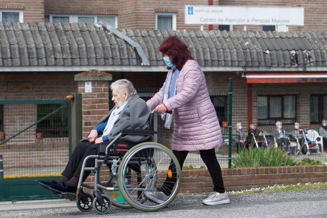 Archivo - Una mujer pasea a una anciana en silla de ruedas, en las inmediaciones de la residencia geriátrica de As Gándaras para visitar a un familiar, a 17 de abril de 2021, en Lugo, Galicia (España). Una de las nuevas medidas incluidas en la desescalada