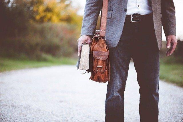Hombre paseando con un libro.