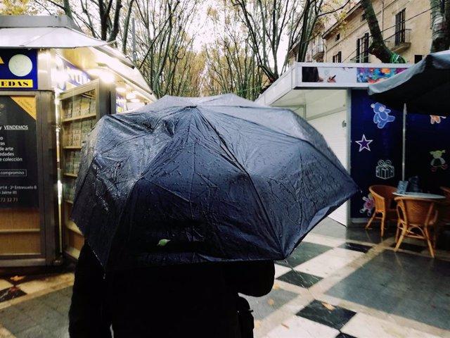 Archivo - Un hombre pasea por la Rambla de Palma bajo un paraguas un día de lluvia.