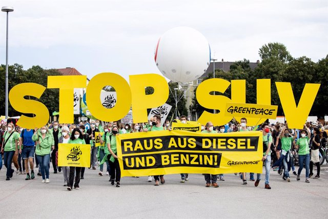 """11 September 2021, Bavaria, Munich: People march with a sign reading """"STOP SUV"""" during a demonstration following a cycling protest against the International Motor Show (IAA Mobility), which runs until 12 September 2021. Photo: Matthias Balk/dpa"""