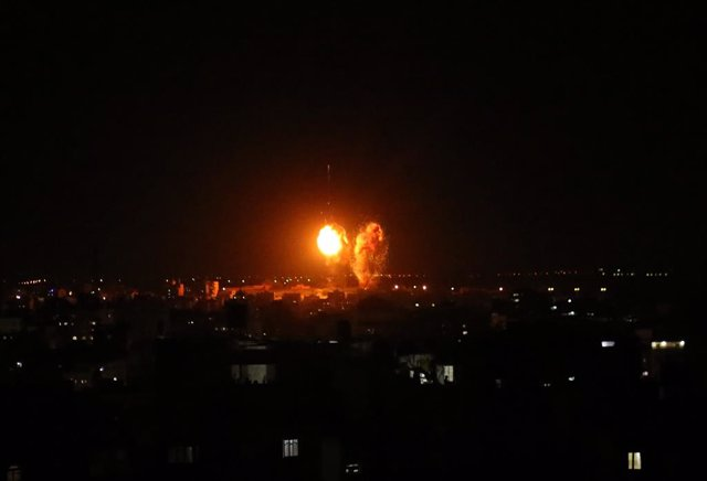 Archivo - 17 June 2021, Palestinian Territories, Gaza City: Explosions light-up the night sky above buildings in Gaza City as Israeli forces shell the Palestinian enclave. The Israeli military tweeted on Thursday night that the bombardments of military co