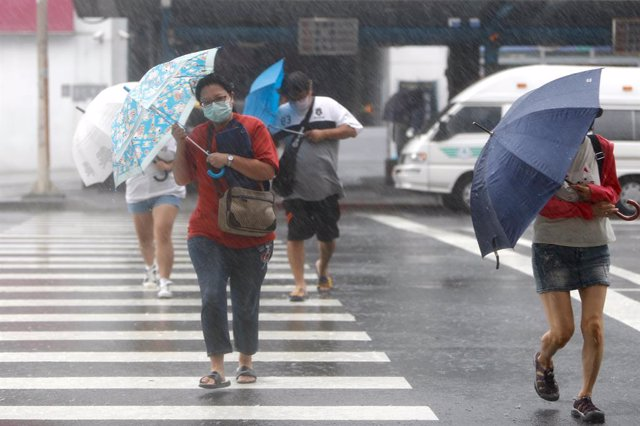 12 September 2021, Taiwan, Keelung: People hold umbrellas as they cross a cross-walk in Keelung as Typhoon Chanthu hits Taiwan with lasting effects on China and Japan. Schools and businesses have been closed in some parts of Taiwan to prevent injuries and